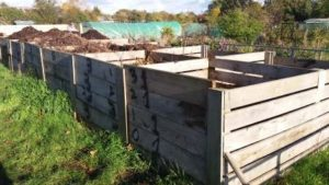 photograph of a community composting set up, showing several homemade wooden composters