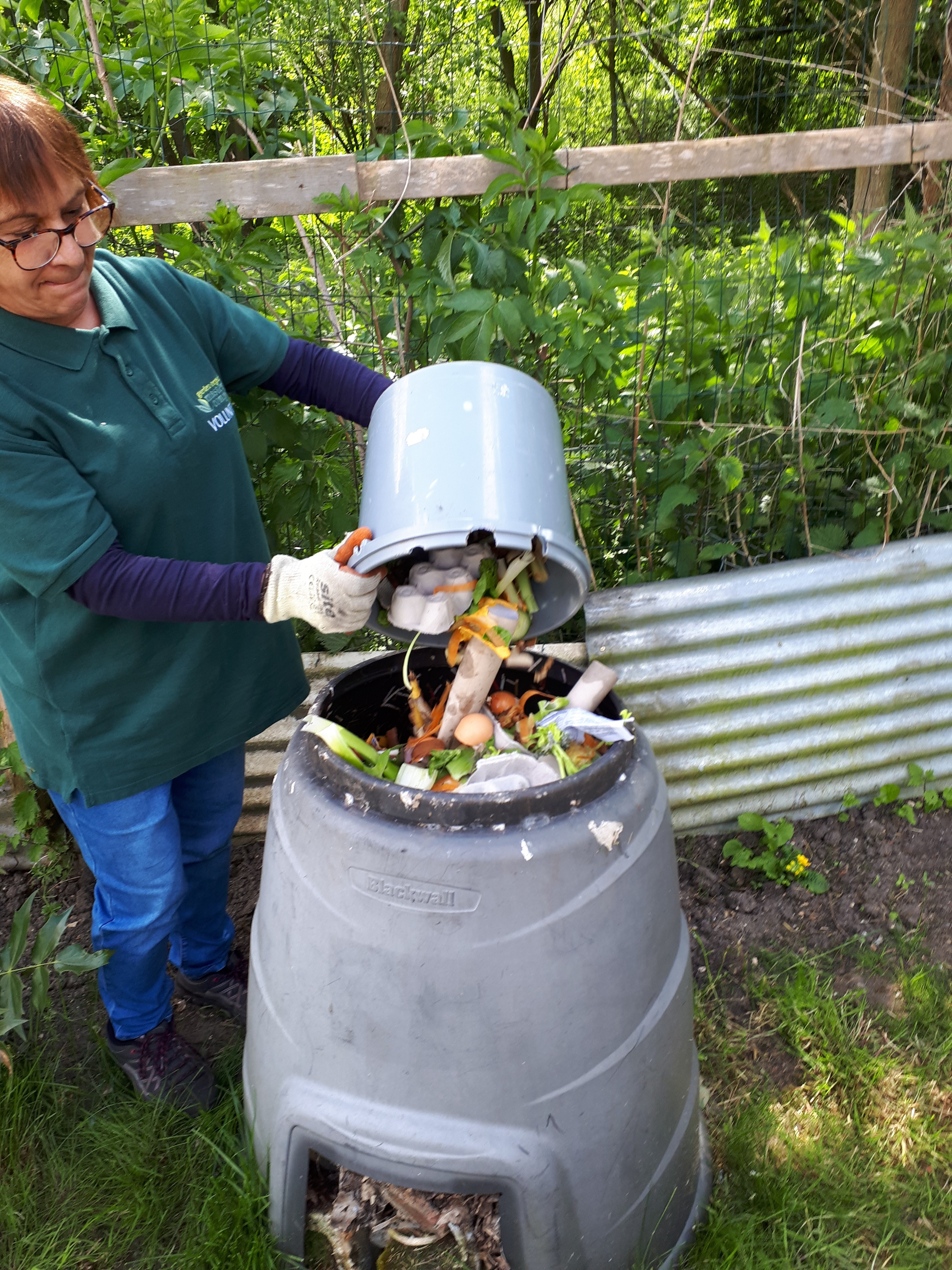 Photograph of Master Composter Anne Wiltshire using her home compost bin